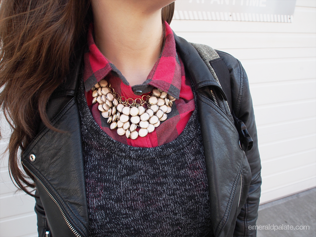 This bauble statement necklace adds a ton of texture interest to the marled sweater, plaid collard shirt, and leather jacket.