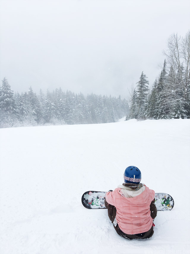 Snowboarder taking in the view of the runs at Schweitzer Mountain Resort in Idaho