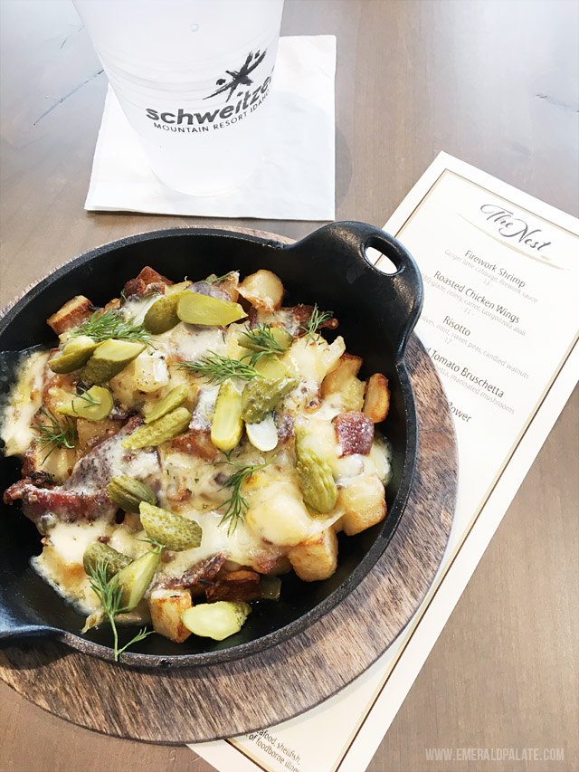 Raclette served with potatoes, bacon, cornichons, and dill. Served at The Nest on Schweitzer Mountain Resort, the lodge at the top of this popular ski resort.