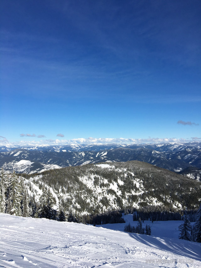The view from the top of Silver Mountain Resort in Idaho. All you see is evergreens, snow, and mountains for days while snowboarding at this popular ski resort in Idaho.